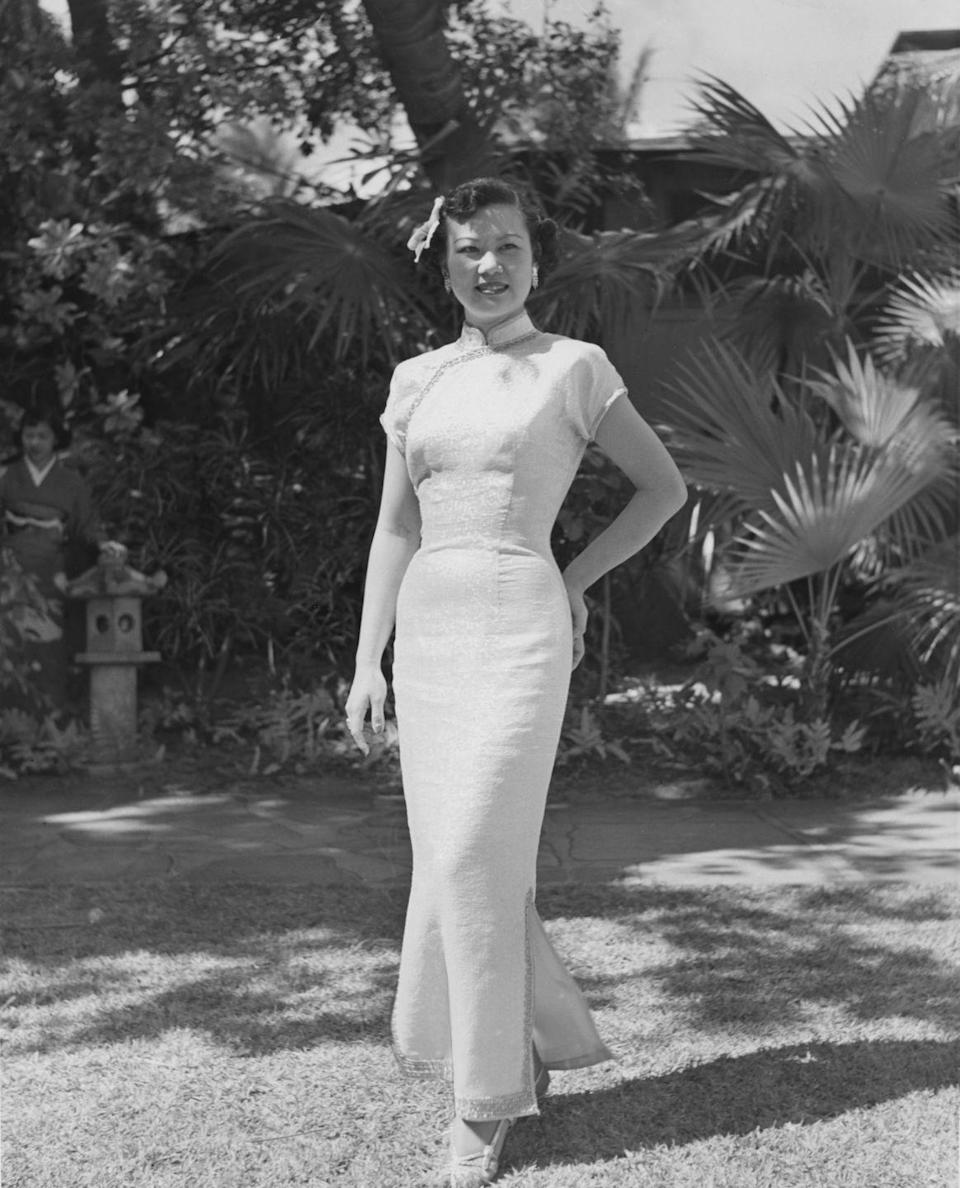 <p>A young woman wearing a brocade cheongsam with strappy sandals and a matching headpiece.</p>