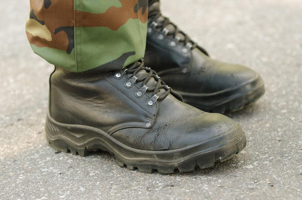 Feet of soldier in black military boots and woodland uniform