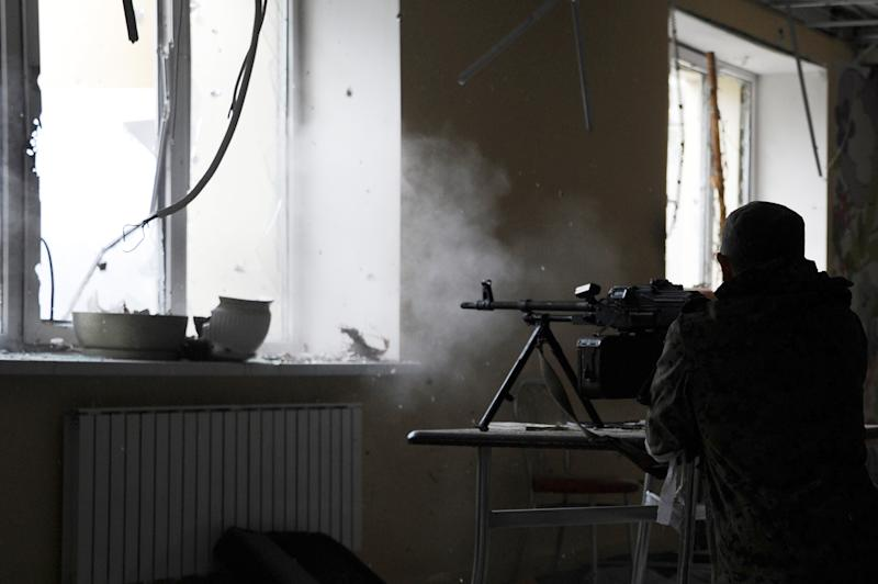 A pro-Russian separatist soldier fires through a window at the Donetsk's Sergey Prokofiev international airport during a shelling between Ukrainian army forces and pro-Russian separatist soldiers on October 16, 2014 (AFP Photo/Dominique Faget)
