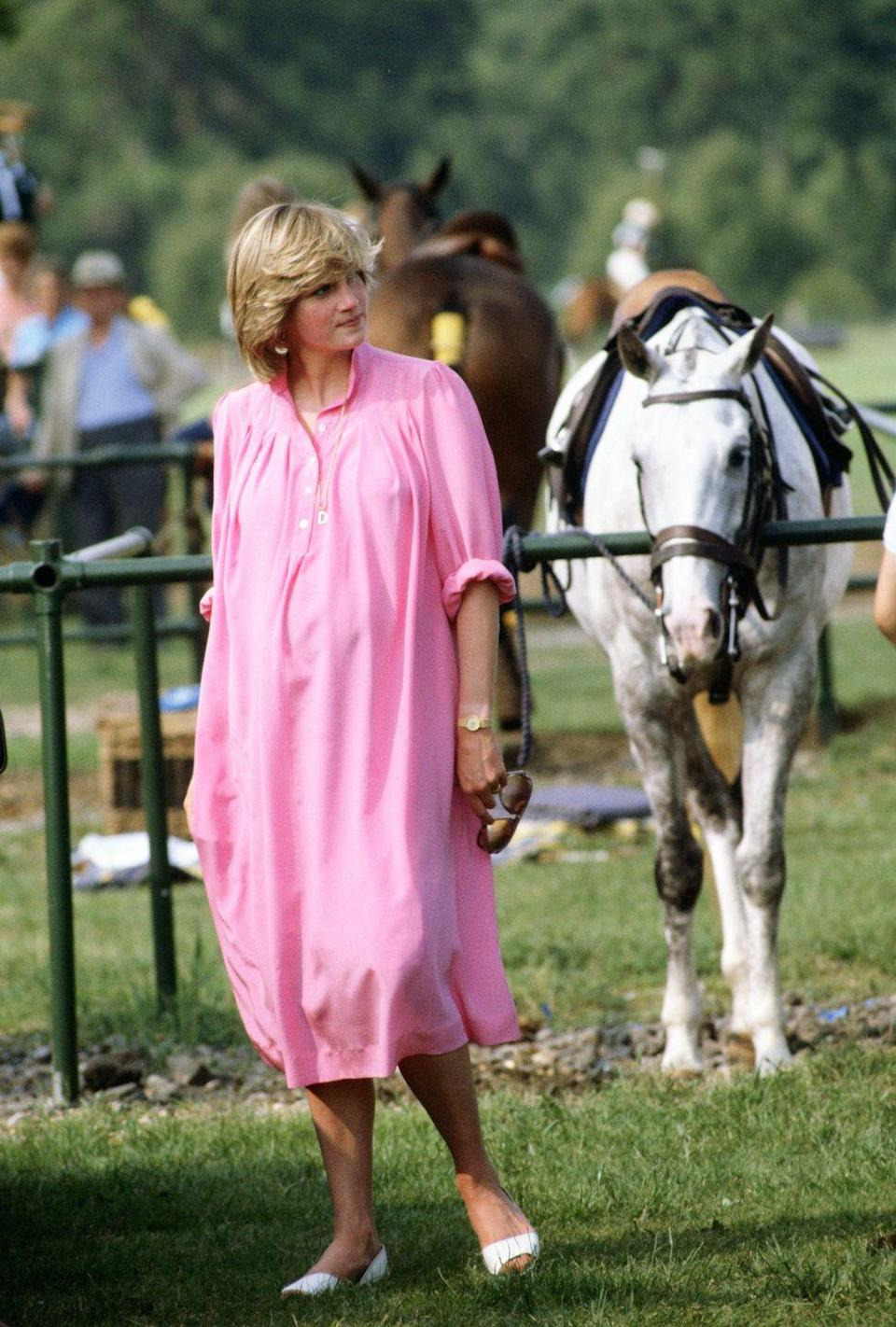 <p>Diana went breezy and casual with a loose pink dress and white flats to watch a polo match in Windsor in June 1982.</p>