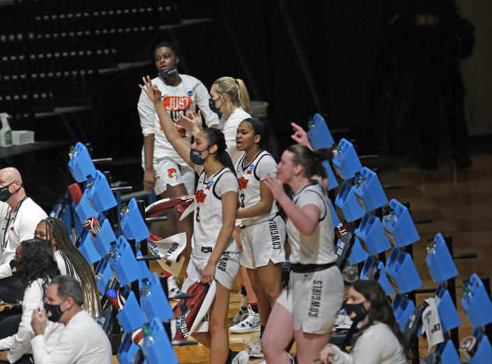 Oklahoma State bench cheer a basket during the first half of a college basketball game against Wake Forest in the first round of the women's NCAA tournament at the Greehey Arena in San Antonio, Texas, Sunday, March 21, 2021. (AP Photo/Ronald Cortes)
