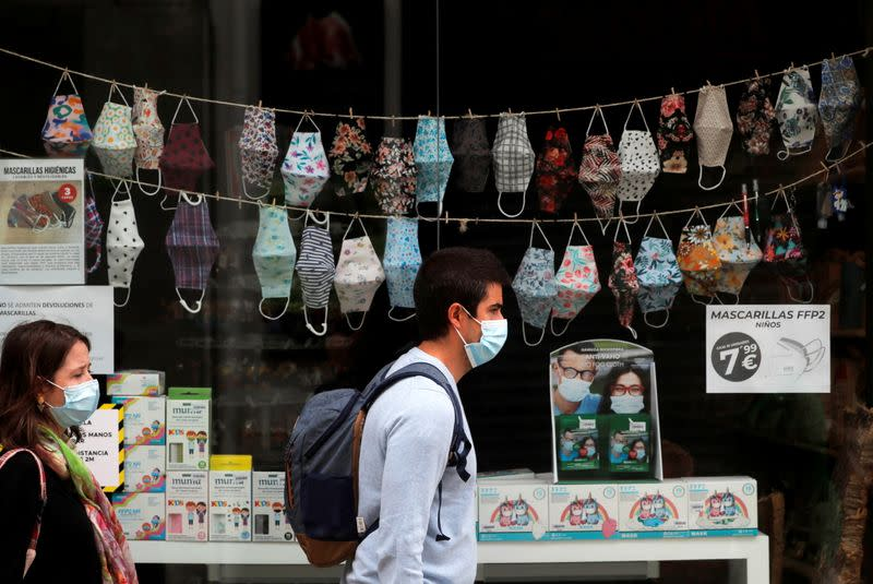 FILE PHOTO: People wear protective masks as they walk past to a souvenir shop with masks displayed in Ronda