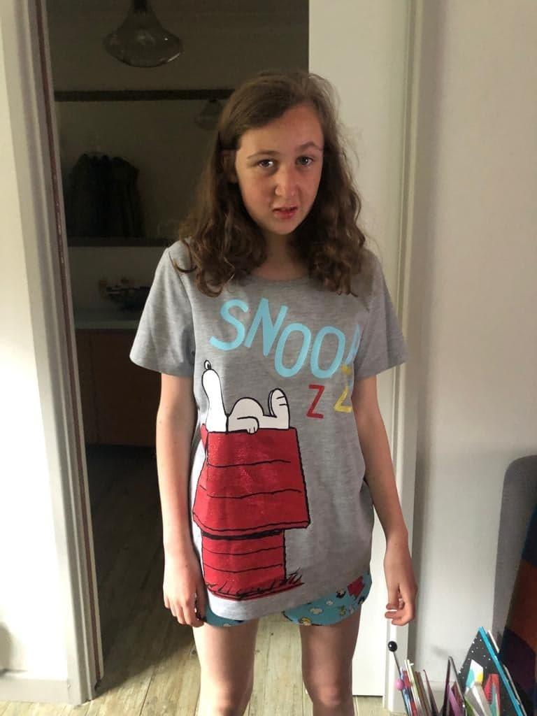A file photo of Nora Quoirin in a grey Snoopy T-shirt shirt.