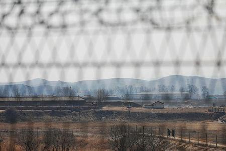 North Korean soldiers patrol behind a border fence near the North Korean town of Sinuiju and Dandong in China's Liaoning province, March 31, 2017. REUTERS/Damir Sagolj