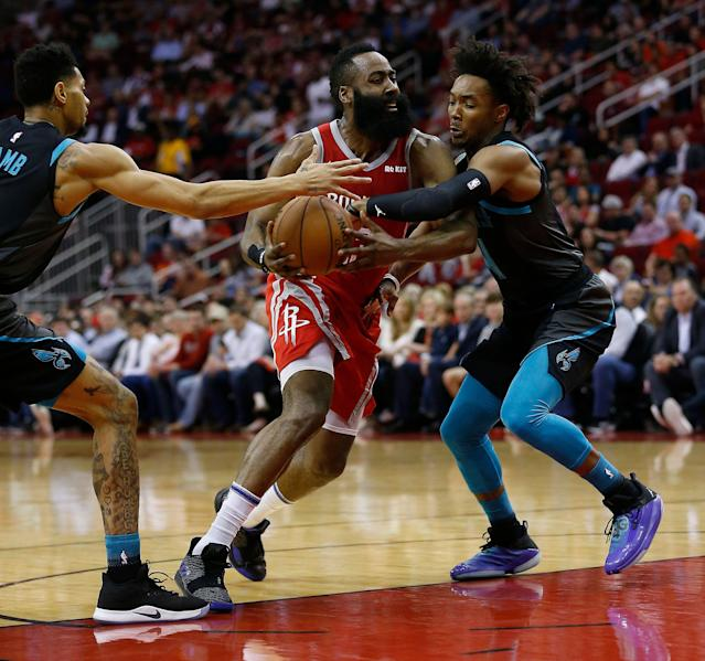 James Harden drives to the basket between Jeremy Lamb (L) and Devonte' Graham of the Hornets on Monday night. (Getty Images)
