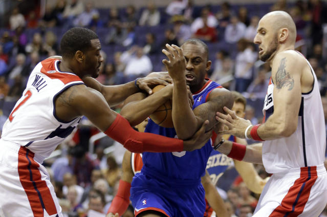 Washington Wizards guard John Wall (2) combines with center Marcin Gortat (4), from Poland, to defend Philadelphia 76ers guard James Anderson in the first half of an NBA basketball game, Friday, Nov. 1, 2013, in Washington. (AP Photo/Alex Brandon)