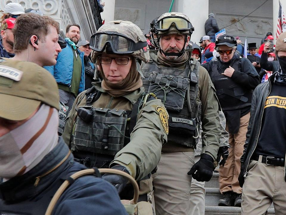 <p>Jessica Marie Watkins (2nd from Left) and Donovan Ray Crowl (Center), both from Ohio, march down the East front steps of the US Capitol with the Oath Keepers militia group</p> (REUTERS)