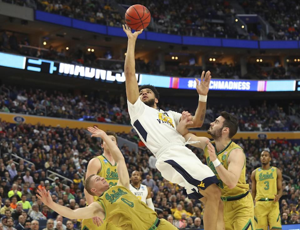<p>West Virginia forward Esa Ahmad (23) goes to the basket against Notre Dame guard Rex Pflueger (0) and guard Matt Farrell (5) during the first half of a second-round men's college basketball game in the NCAA Tournament, Saturday, March 18, 2017, in Buffalo, N.Y. (AP Photo/Bill Wippert) </p>