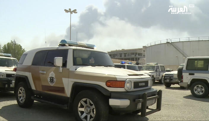 In this image made from a video broadcast on the Saudi-owned Al-Arabiya satellite news channel on Saturday, Sept. 14, 2019, a Saudi police cruiser sits in a parking lot as the smoke from a fire at the Abqaiq oil processing facility can be seen behind it in Buqyaq, Saudi Arabia. Drones launched by Yemen's Houthi rebels attacked the world's largest oil processing facility in Saudi Arabia and another major oilfield Saturday, sparking huge fires at a vulnerable chokepoint for global energy supplies. (Al-Arabiya via AP) TV OUT NO SALES