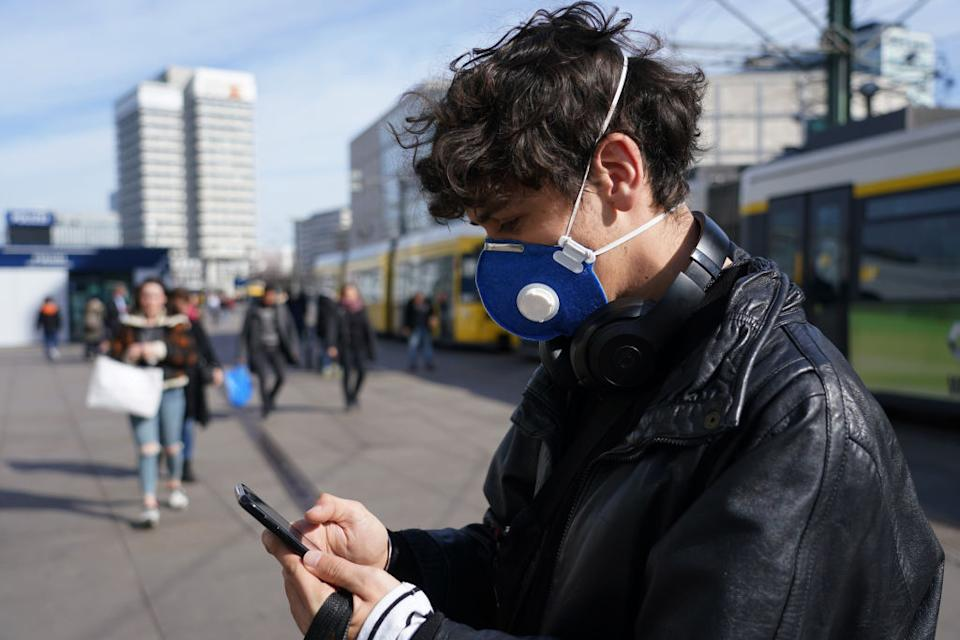 A young man visiting from Brazil and wearing a protective face mask against the coronavirus checks his smartphone while walking across Alexanderplatz in Berlin, Germany.