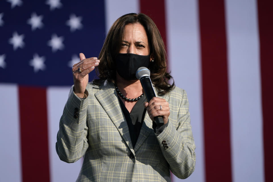 Sen. Kamala Harris speaks into a microphone wearing a black face mask and standing in front of an American flag