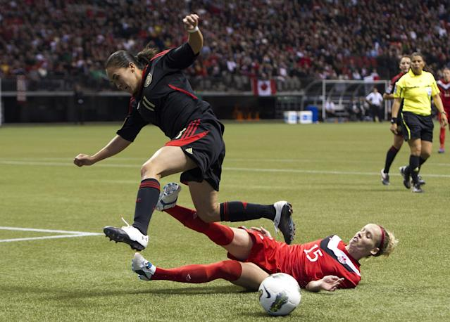 VANCOUVER, CANADA - JANUARY 27: Kelly Parker #15 of Canada makes a sliding tackle to knock the ball away from Monica Ocampo #11 of Mexico during the second half of semifinals action of the 2012 CONCACAF Women's Olympic Qualifying Tournament at BC Place on January 27, 2012 in Vancouver, British Columbia, Canada. (Photo by Rich Lam/Getty Images)
