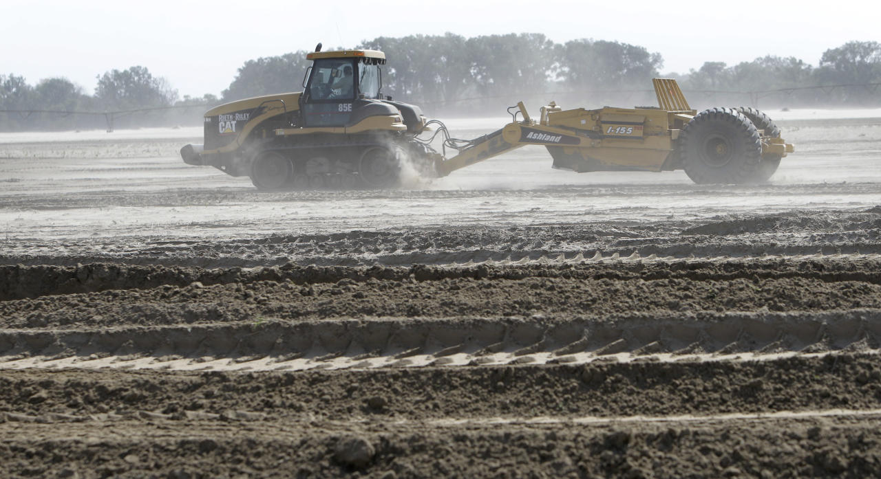 In this May 22, 2012, photo, heavy equipment is used to move sand in a farm field in Missouri Valley, Iowa. Hundreds of farmers in Iowa and Nebraska are still struggling to remove sand and fill holes gouged by the Missouri River, which swelled last summer with rain and snowmelt and overflowed onto thousands of acres of farmland. (AP Photo/Charlie Neibergall)