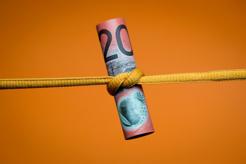 Close up of an Australian twenty dollar note tied in a knot. Studio shot on orange background.