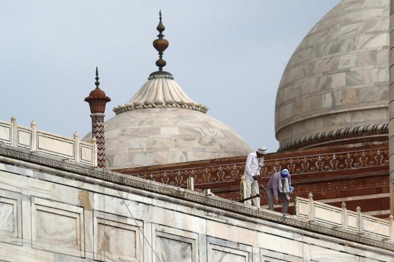 Workers stand on a railing of the Taj Mahal after parts of the complex were damaged in a heavy thunderstorm on Friday