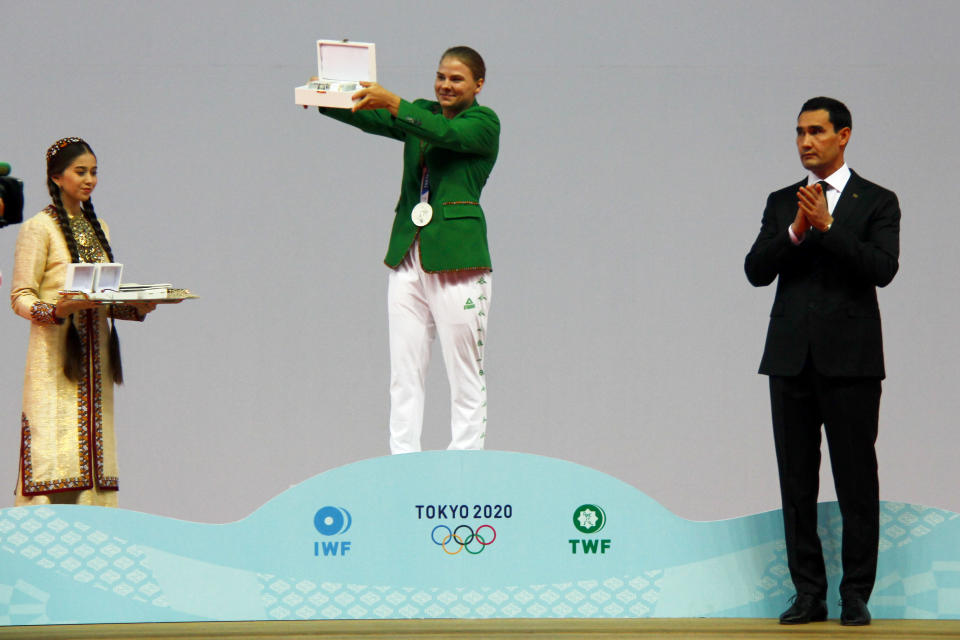 Polina Guryeva, Olympic silver medalist in the women's 59kg weightlifting event, at the 2020 Summer Olympics, center, shows her Presidential gift as Turkmenistan's authoritarian president, Gurbanguly Berdymukhamedov's son Serdar, who was recently promoted to deputy prime minister, applauds her at a lavish ceremony in Ashgabat, Turkmenistan, Saturday, Aug. 21, 2021. Turkmenistan has lauded its first Olympic medal winner at a lavish ceremony where she was showered with gifts. Guryeva, 21, lifted a total 217 kilograms in the 59-kilogram category, edging Mikiko Andoh of Japan for second place at the Tokyo Games. (AP Photo/Alexander Vershinin)