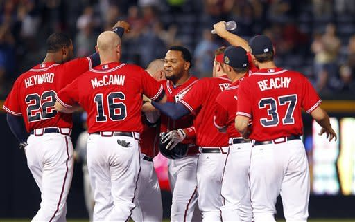 Atlanta Braves player mob pinch hitter Juan Francisco, center, after he drove in the game-winning run with a base hit in the 11th inning of a baseball game against the Los Angeles Dodgers, Friday, Aug. 17, 2012, in Atlanta. Atlanta won 4-3.(AP PhotoJohn Bazemore)