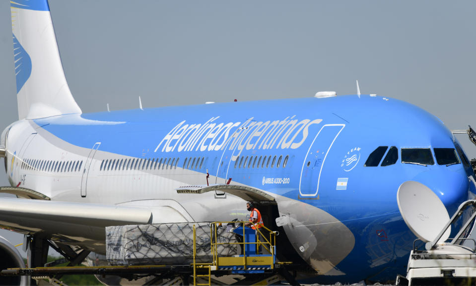 Workers unload the first shipment of Russia's Sputnik V COVID-19 vaccine from an airplane at the international airport in Buenos Aires, Argentina, Thursday, Dec. 24, 2020. (AP Photo/Gustavo Garello)