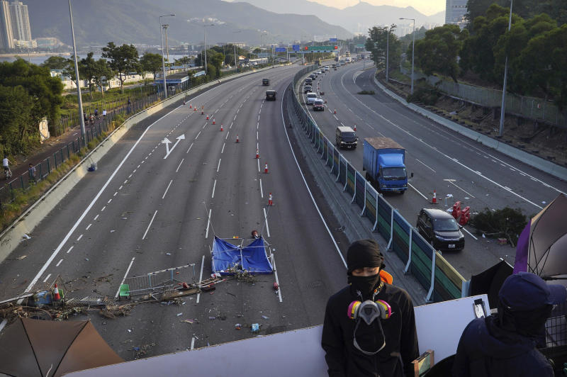 A protester stands on a barricaded bridge as traffic passes underneath near the Chinese University of Hong Kong in Hong Kong, Friday, Nov. 15, 2019. Protesters who had barricaded themselves in a Hong Kong university this week began to leave Friday after partially clearing a road they had blocked and demanding that the government commit to going ahead with local elections on Nov. 24. (AP Photo/Vincent Yu)