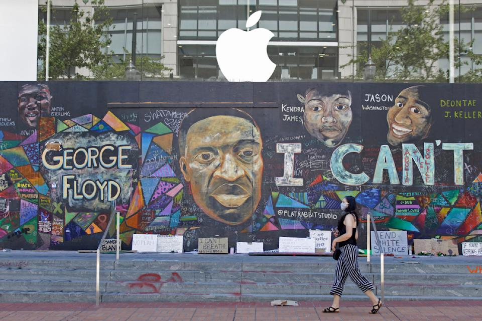 A pedestrian walks past a boarded-up Apple store that's been covered in street art in downtown Portland, Ore., Monday, July 13, 2020. While most demonstrations in the city have been peaceful, nightly violent clashes between police and protesters have divided Portland, paralyzed the downtown and attracted the attention of President Donald Trump, who sent federal law enforcement to the city to quell the unrest. (AP Photo/Gillian Flaccus)