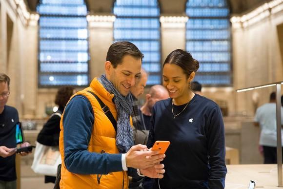 An Apple customer and an Apple Store employee both looking at an orange iPhone XR.