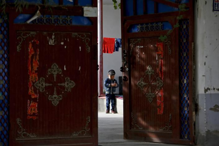 FILE - In this Sept. 20, 2018, file photo, an Uighur child plays alone in the courtyard of a home at the Unity New Village in Hotan, in western China's Xinjiang region. The prominent British human rights lawyer Geoffrey Nice is convening an independent tribunal in London with public hearings in 2021, to look into the Chinese government's alleged rights abuses against the Uighur Muslim minority in the far western province of Xinjiang.(AP Photo/Andy Wong, FILE)