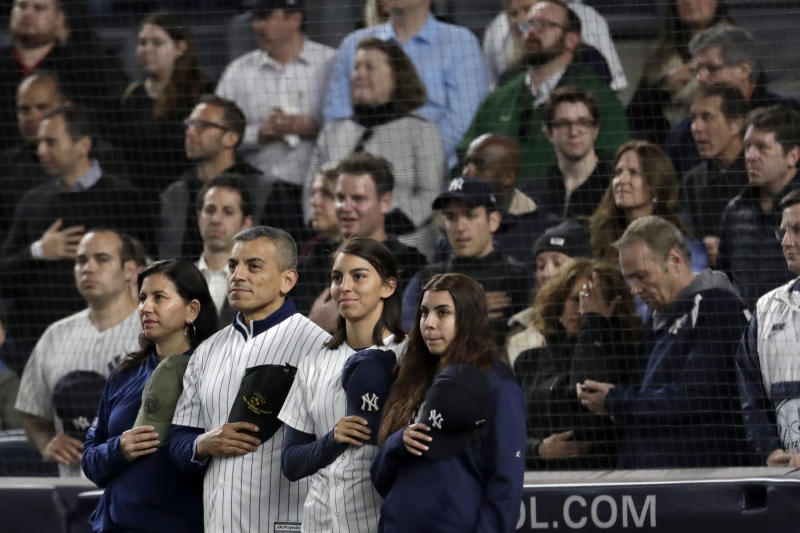 "Marine Corps Lt. Col. Manuel Merino, second from left, of New York, who served in Operation Iraqi Freedom, stands with his family as they listen to ""God Bless America"" during the seventh-inning stretch of a baseball game between the New York Yankees and the Kansas City Royals, Thursday, April 18, 2019, in New York. The Yankees have suspended the use of Kate Smith's recording of ""God Bless America"" while they investigate an allegation of racism against the singer. The New York Daily News reported there are conflicting claims about Smith's 1939 song ""That's Why Darkies Were Born."" The song originated in the 1931 Broadway review ""George White's Scandals,"" and was considered satire. It was recorded by Smith and by Paul Robeson, who was black. (AP Photo/Julio Cortez)"