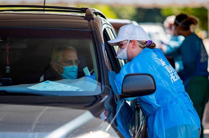 Tidelands Health medical professionals conduct a drive-through COVID-19 testing site in July at Myrtle Beach Pelicans Ballpark.