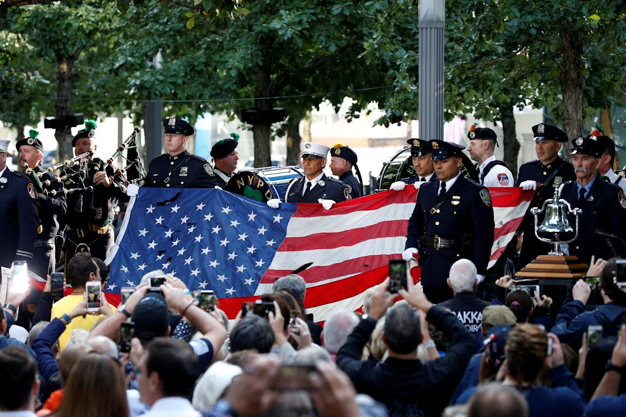 REFILE - CORRECTING BYLINE Police and Fire Department officers hold an American flag that flew over the World Trade Centre at the National 911 Memorial and Museum during ceremonies marking the 16th anniversary of the September 11, 2001 attacks in New York, U.S. September 11, 2017.  REUTERS/Brendan McDermid