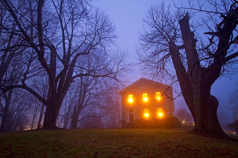 Old stone house with candles in window on foggy gloomy night. Source: Getty