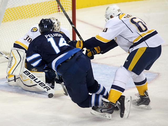 Winnipeg Jets' Anthony Peluso (14) is tripped by Nashville Predators' Victor Bartley (64) in front of goaltender Carter Hutton (30) during first period NHL hockey game in Winnipeg, Manitoba, Sunday, Oct. 20, 2013. (AP Photo/The Canadian Press, Trevor Hagan)