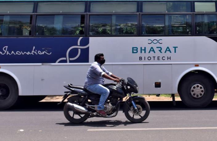 FILE PHOTO: A man rides his motorcycle past a parked bus of Indian biotechnology company Bharat Biotech outside its office in Hyderabad