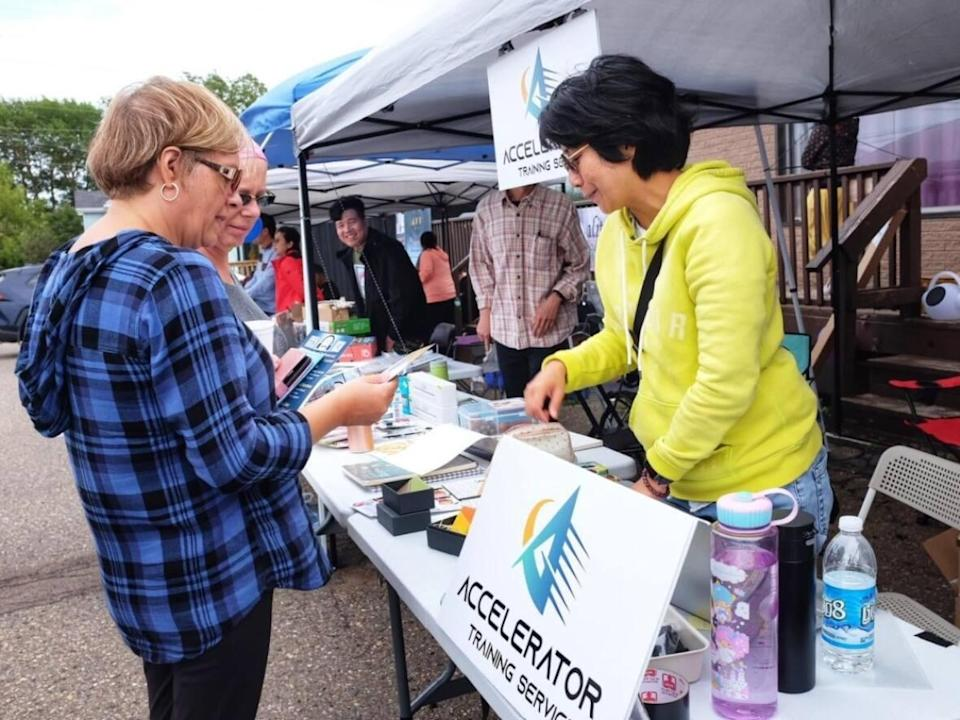 Heidi Lai, right, owner of Accelerator Training Services, talks to people who dropped by the Asia Market in Summerside last month. She's organizing another one in O'Leary in November. (Accelerator Training Services/Facebook - image credit)