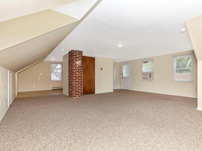 An open lofted apartment with a brick column in the background