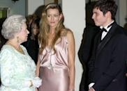 <p>While attending the premiere of <em>The Truman Show, </em>actress Natascha McElhone chatted with Queen Elizabeth while wearing a slinky, pink silk dress. </p>