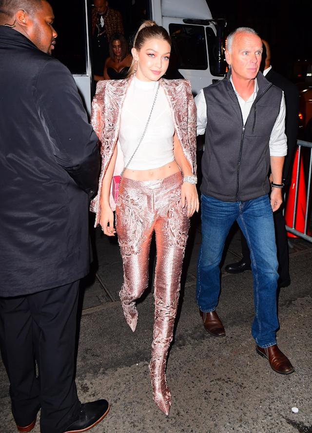 <p>Gigi Hadid shined in a pink metallic suit and white crop top. (Photo: Splash News) </p>