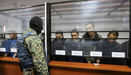 Islamic State supporters, who attacked a National Guard facility in June, sit inside a glass-walled cage during a verdict hearing at a court in Aktobe, Kazakhstan, November 28, 2016.  REUTERS/Stringer