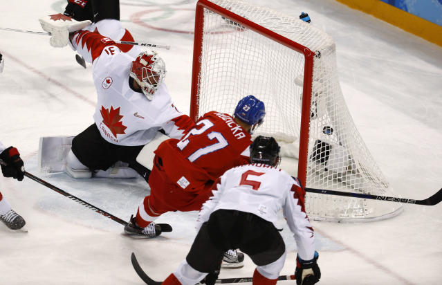 Martin Ruzicka (27), of the Czech Republic, scores a goal past goalie Kevin Poulin (31), of Canada, during the first period of the men's bronze medal hockey game at the 2018 Winter Olympics in Gangneung, South Korea, Saturday, Feb. 24, 2018. (AP Photo/Charlie Riedel)
