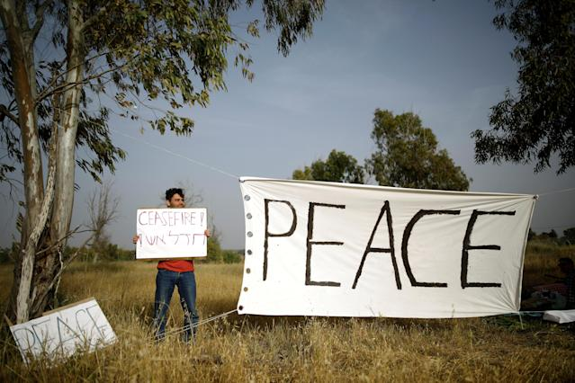<p>An Israeli peace activist holds a sign in front of the Israel-Gaza border, as Palestinians protest on the Gaza side of the border near Kibbutz Nahal Oz, Israel, April 5, 2018. (Photo: Amir Cohen/Reuters) </p>
