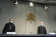 Mons. Filippo Iannone, right, and Mons. Juan Ignacio Arrieta Ochoa de Chinchetru arrive for a press conference to illustrate changes in the Church's Canon law, at the Vatican, Tuesday, June 1, 2021. Pope Francis has changed church law to explicitly criminalize the sexual abuse of adults by priests who abuse their authority and to say that laypeople who hold church office can be sanctioned for similar sex crimes. (AP Photo/Andrew Medichini)