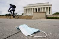 FILE PHOTO: A cyclist passes a discarded face mask in front of the Lincoln Memorial during the coronavirus disease (COVID-19) pandemic in Washington