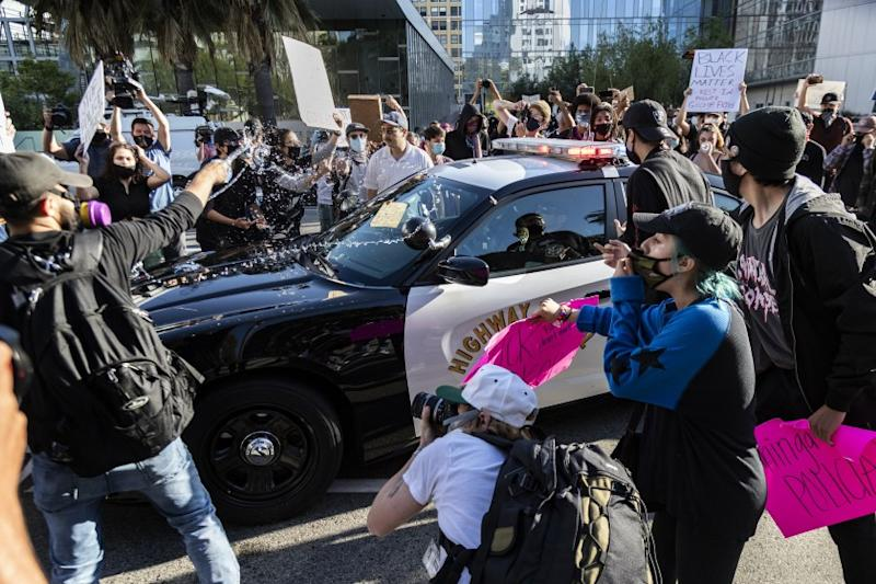 LOS ANGELES, CA - MAY 28, 2020: A protester tosses a bottled water on a CHP vehicle as other Black Lives Matter protesters swarm the car in a rally in front of LAPD headquarters to protest the death of George Floyd during the coronavirus pandemic on May 28, 2020 in Los Angeles, California. (Gina Ferazzi / Los Angeles Times)