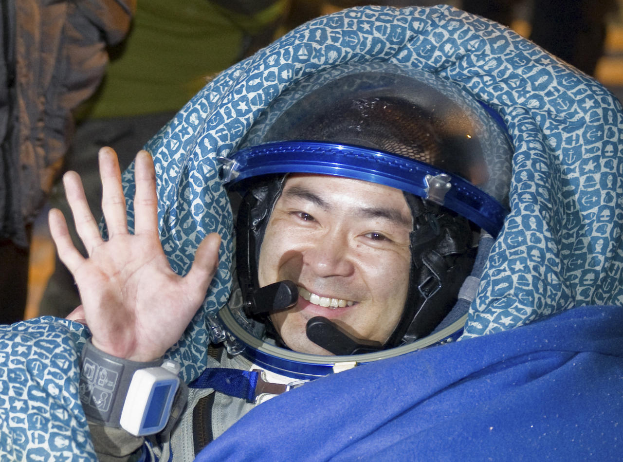 Japanese astronaut Aki Hoshide waves shortly after landing near the town of Arkalyk, northern Kazakhstan, Monday, Nov. 19, 2012. Japanese astronaut Aki Hoshide, Russian cosmonaut Yury Malenchenko and U.S. astronaut Sunita Williams,  touched down in the dark, chilly expanses of central Kazakhstan onboard a Soyuz capsule Monday after a 125-day stay at the International Space Station. (AP Photo/Sergei Remezov, Pool)