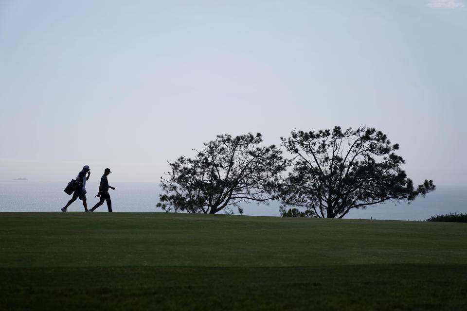 Justin Rose, of England, right, and his caddy walk up the fourth fairway during the first round of the U.S. Open Golf Championship, Thursday, June 17, 2021, at Torrey Pines Golf Course in San Diego. (AP Photo/Gregory Bull)