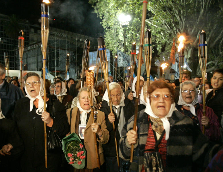 FILE - This a Monday, April 30, 2007 file photo of Argentina's Mothers of Plaza de Mayo hold torches as they rally with torches to mark the 30th anniversary of their first protest around Buenos Aires Plaza de Mayo to demand the return of their disappeared children on April 30, 1977. Tens of thousands of people throughout the world are listed as missing in armed conflicts and after illegal arrests, detentions, abduction or any other form of deprivation of human rights and liberty. On the International Day of the Disappeared on Thursday Aug.30, 2012 the International Commission on Missing Persons (ICMP) called on all governments to provide answers to families on the fate and whereabouts of the missing persons.(AP Photo/Eduardo Di Baia, File)