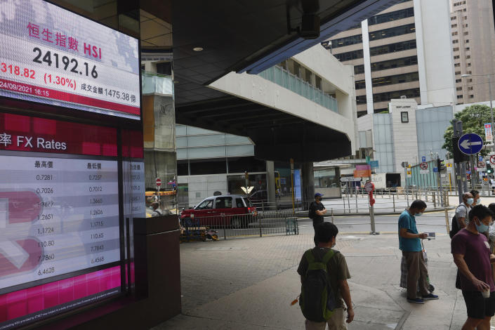 People wearing face masks stand in front of a bank's electronic board showing the Hong Kong share index at Hong Kong Stock Exchange in Hong Kong Monday, Sept. 27, 2021. Asian share rose Monday, but skepticism about the economic outlook for the region tempered the rally amid worries about further waves of COVID-19 outbreaks. (AP Photo/Vincent Yu)