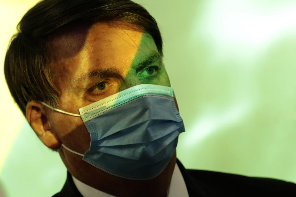 President Jair Bolsonaro wears a mask amid the COVID-19 pandemic at the start of a ceremony where the national flag is projected in Brasilia, Brazil, Wednesday, Aug. 5, 2020. (AP Photo/Eraldo Peres)