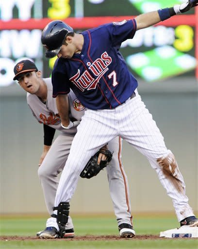 Baltimore Orioles second baseman Ryan Flaherty, left, makes sure Minnesota Twins' Joe Mauer remains on the base after Mauer doubled in the first inning of a baseball game, Tuesday, July 17, 2012, in Minneapolis. (AP Photo/Jim Mone)