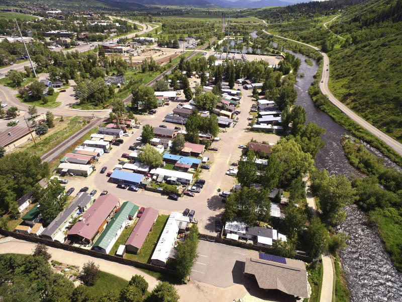 This July 6, 2019, photo shows the Fish Creek Mobile Home Park next to the Yampa River and bike path in Steamboat Springs, Colo. Some Colorado towns are taking action to preserve their remaining mobile home parks. Cities, counties and housing authorities, such as the Yampa Valley Housing Authority in Steamboat Springs, are buying mobile home parks to preserve affordable housing for residents as other mom-and-pop park owners sell out to developers or investors.(Matt Stensland/The Colorado Sun via AP)