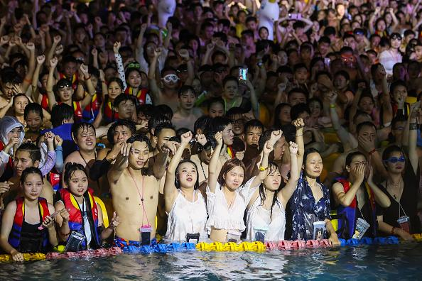 This photo taken shows people watching a performance as they cool off in a swimming pool in Wuhan in China's central Hubei province.